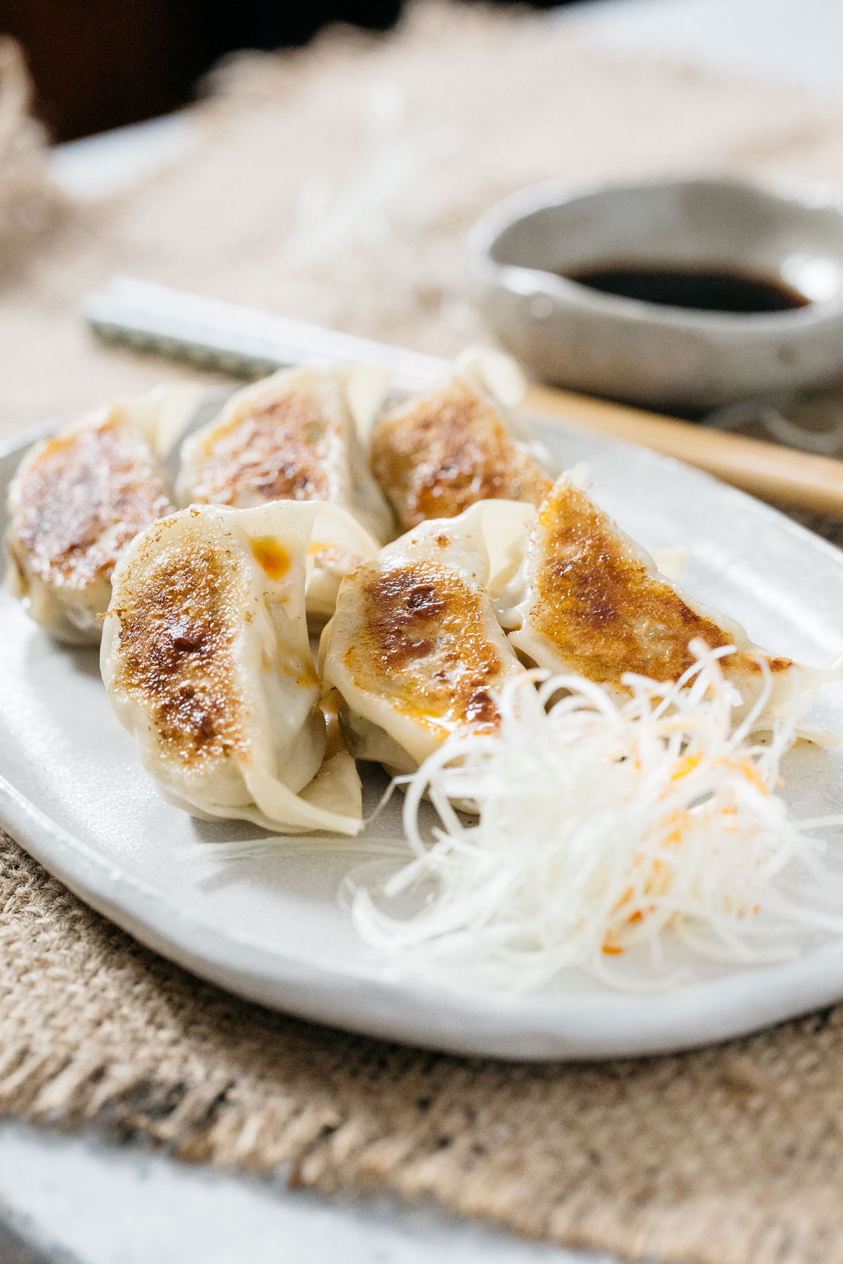 6 Japanese gyoza served on an oval shaped plate