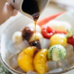 Brown sugar syrup poured over anmitsu fruit and mochi in a japanese pottery bowl