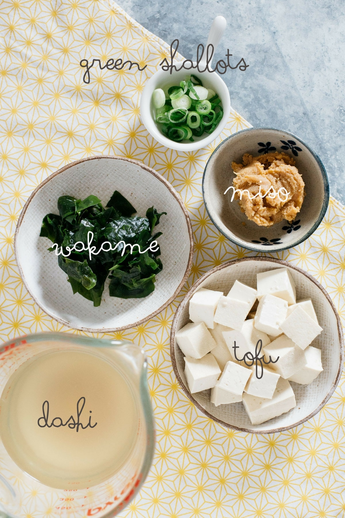 Japanese miso soup ingredients:dashi, miso, tofu, wakame, and green shallots in bowls
