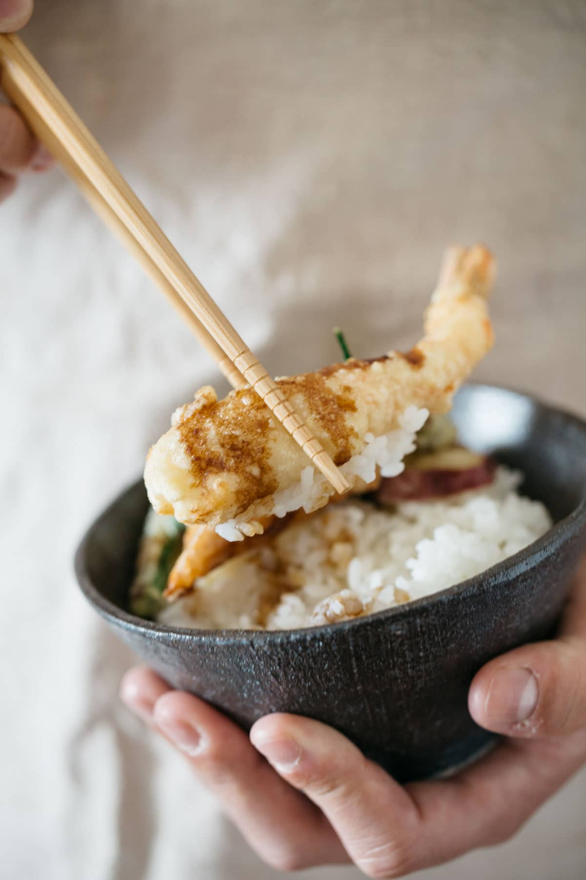 A prawn tempura picked up by a pair of chopstick