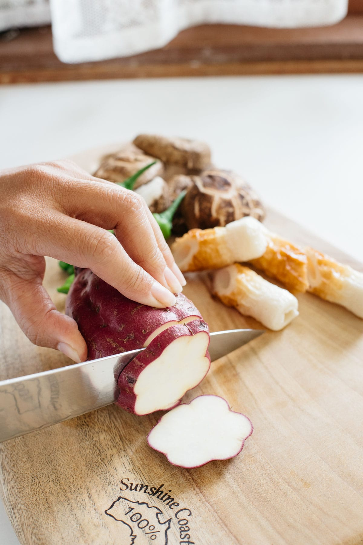 Purple sweet potato being sliced on a chopping board