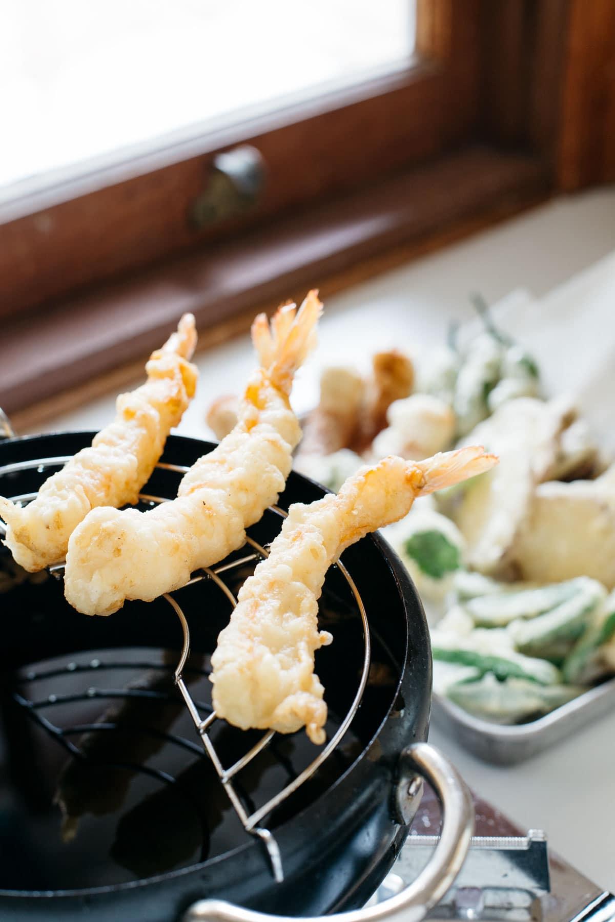 Three prawn tempura just deep fried and resting on a lack