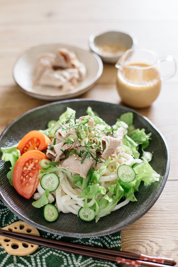 Udon noodle salad topped with shabu shabu pork and spring vegetables such as lettuce and sesame dressing on black plate.