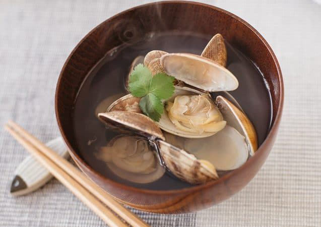 Japanese clear soup with manila clams is served in a wooden bowl with a pair of chopsticks