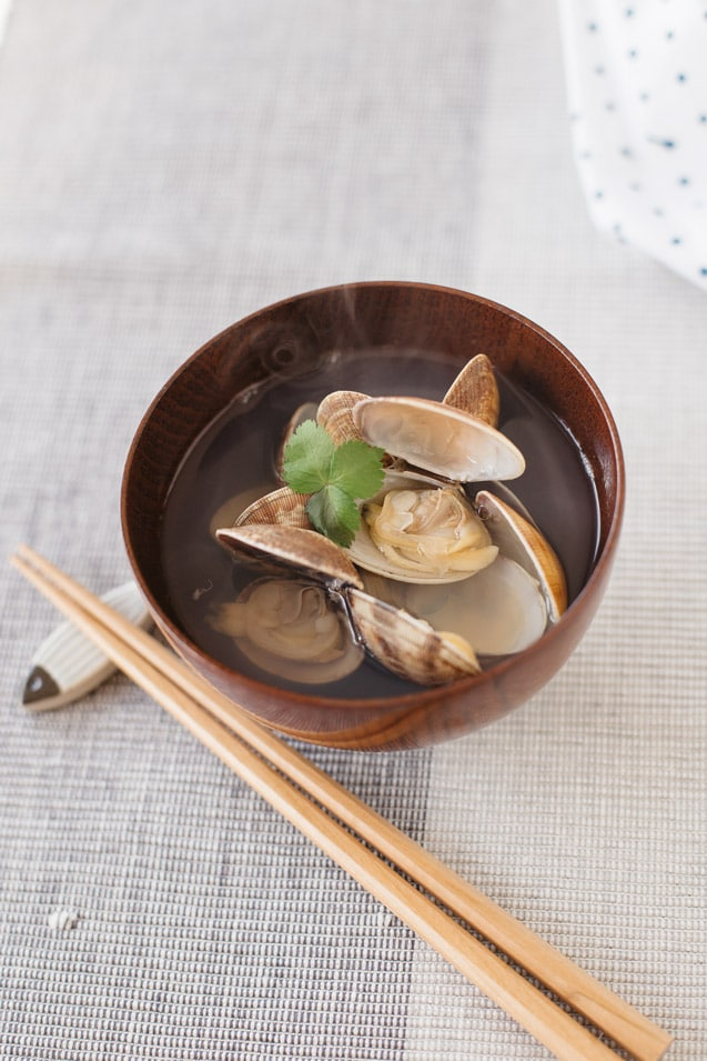 Clam Japanese clear soup is served in a wooden bowl with a pair of chopsticks