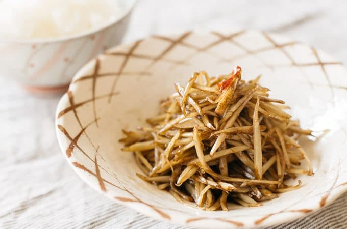 Kinpira gobo served on a bowl with a bowl of rice and a pair of chopsticks