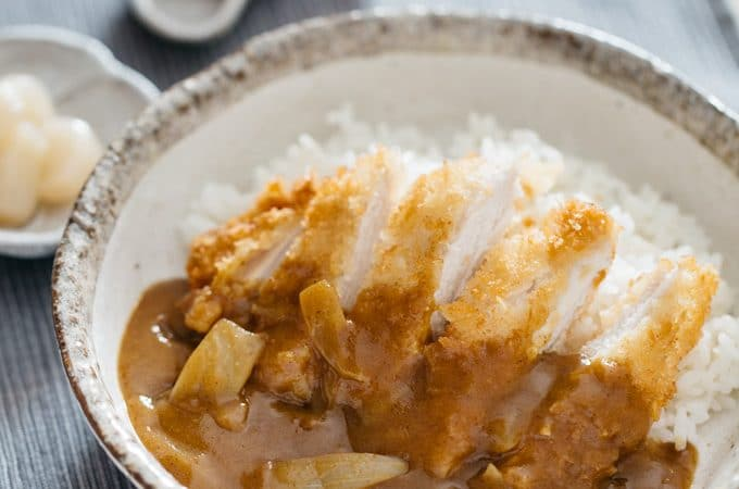 Chicken katsu curry served in a round shallow bowl with a spoon