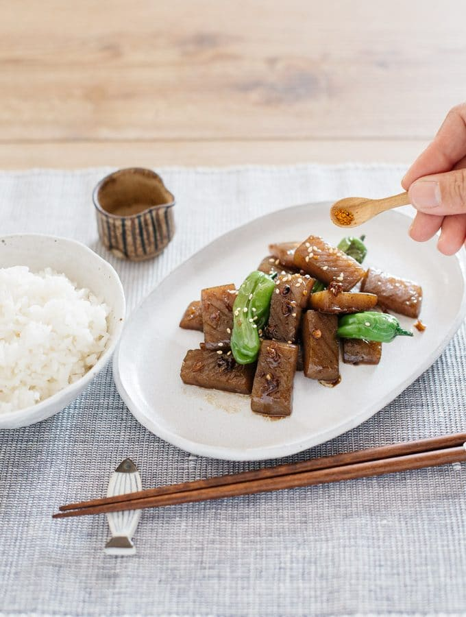 konnyaku steak with shishito peppers served on a oval shaped plate with a bowl of rice, and a pair of chopsticks and Shichimi togarashi being sprincled