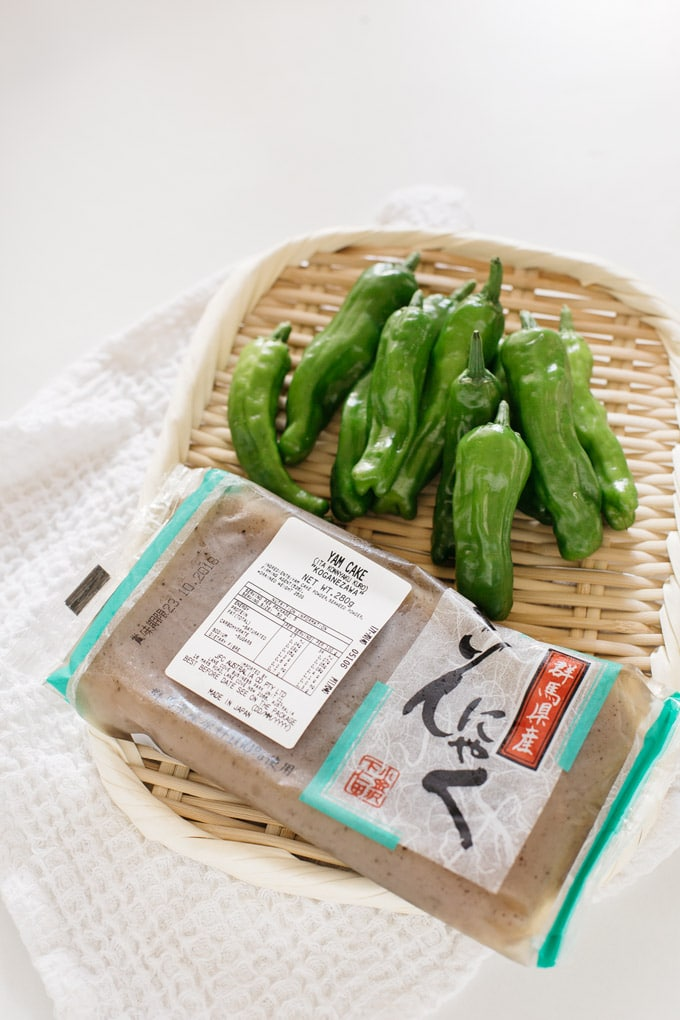 Konnyaku in a packet and shishito peppers on a rectangle bamboo tray