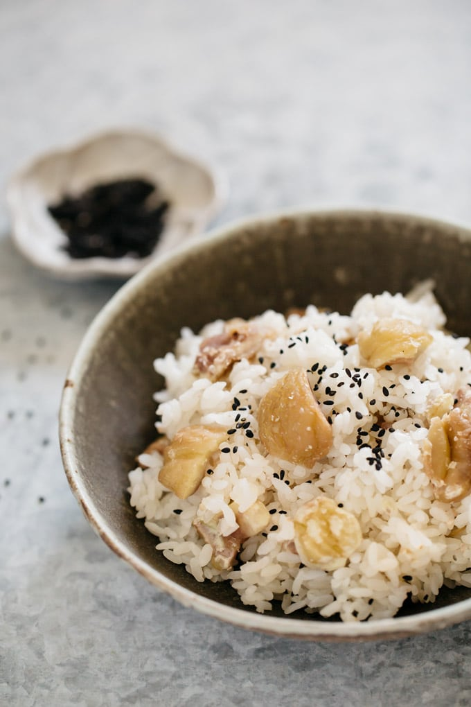 Chestnuts rice served on a round shallow bowl with a small bowl of black sesame seeds