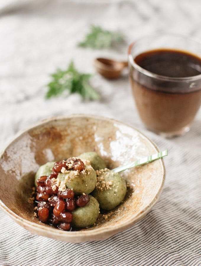 Yomogi dango served in a Japanese pottery bowl with azuki bean paste and kinako powder with iced coffee