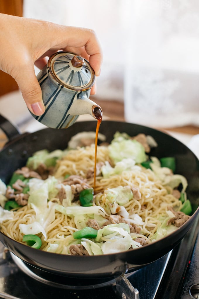Yakisoba sauce being poured over yakisoba in a frying pan