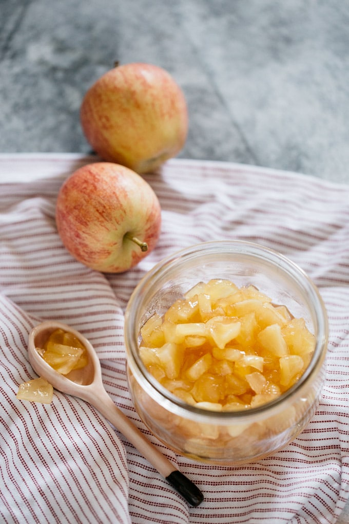 Apple jam in a preserving jar with two apples around and a spoon