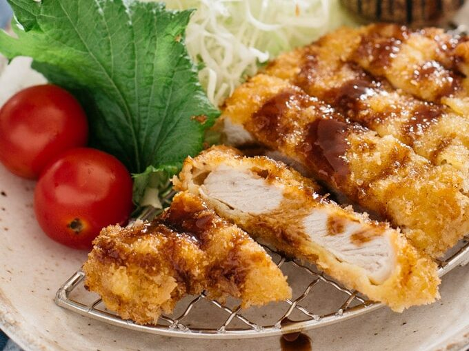 Tonkatsu served on an oval plate with shredded cabbage and tomatoes