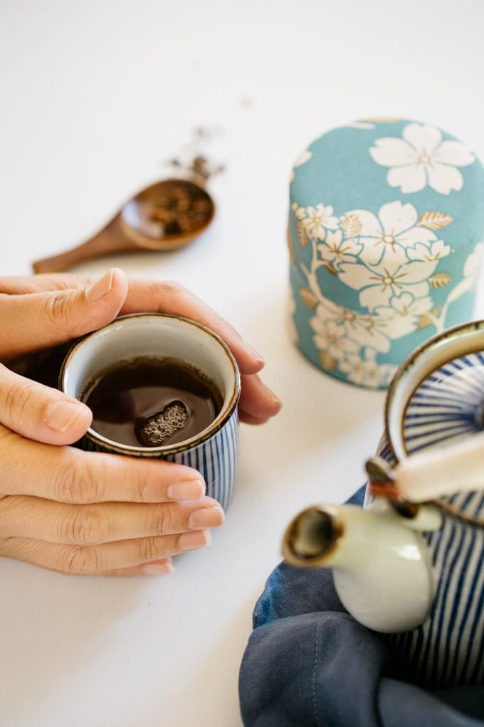 Hojicha brewed in a Japanese tea cup with Japanese tea pot and tea caddey