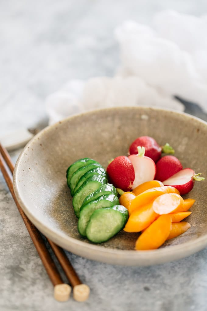 Cucumber, radish, and carrot pickled in rice bran on a round plate with a pair of chopstick