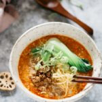 Tantanmen served in a large noodle bowl with a pair of chopstick