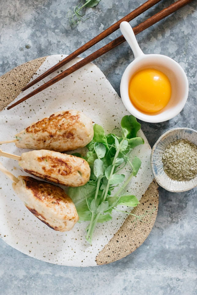 three tsukune chicken skewers on a plate with green salad and a egg yolk