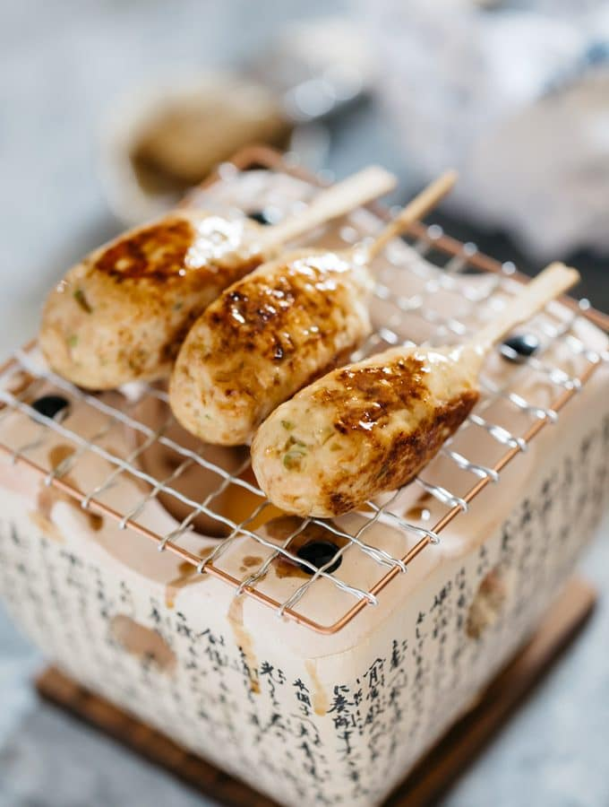 3 Tsukune Chicken meatball on skewers over an individual Japanese style grill