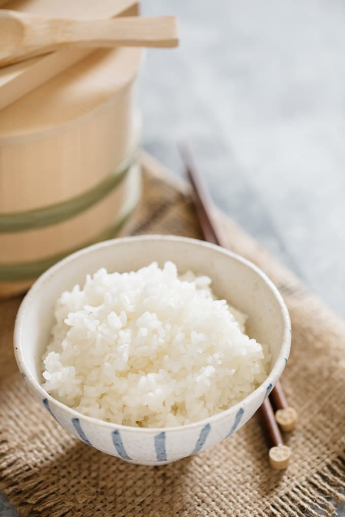 Japanese plain steamed rice in a Japanese rice bowl with a pair of chopstick and wooden container of rice
