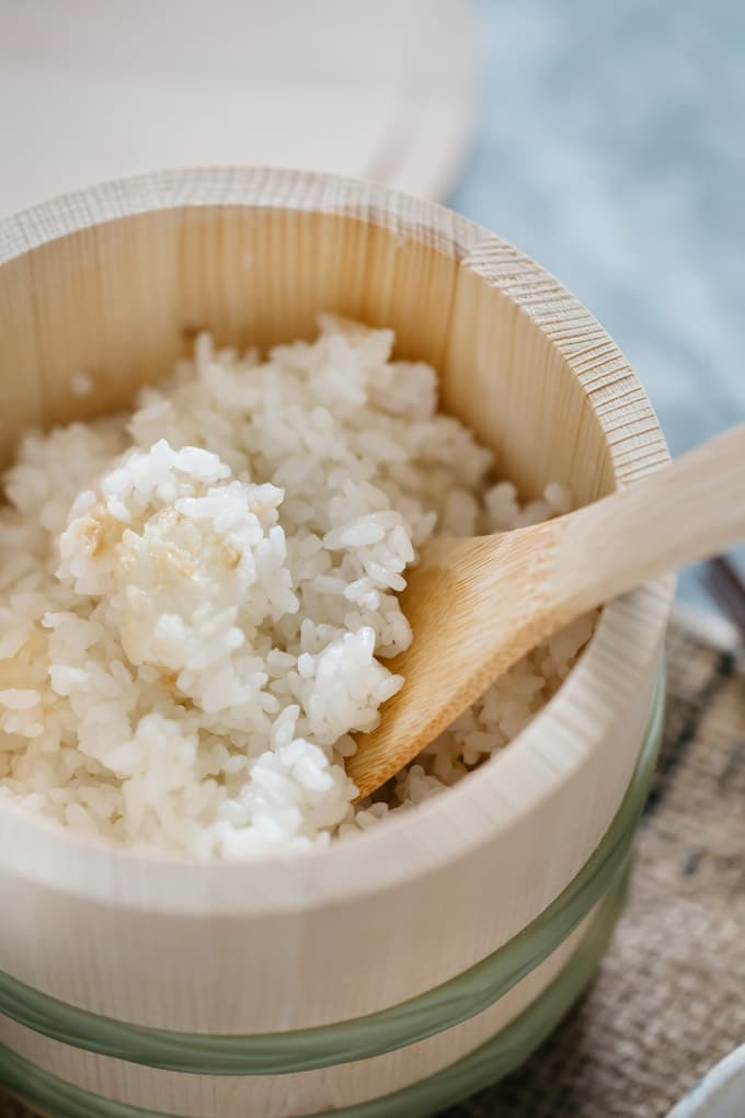 plain steamed rice in a wooden container with a wooden rice spatula