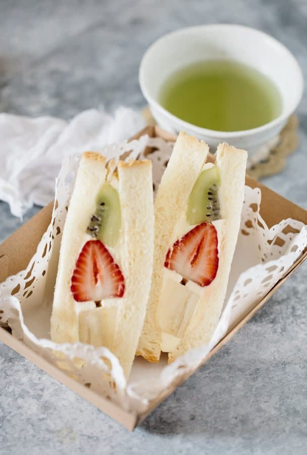 2 pieces of fruit sandwiches on a take away container with a small bowl of creen tea