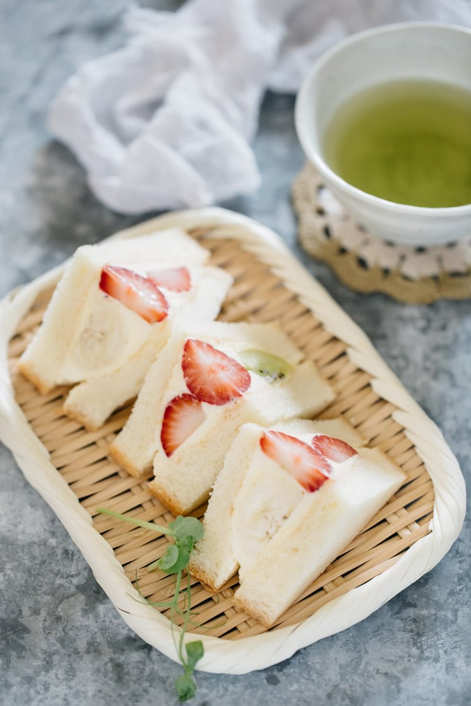 Three pieces of Fruit Sandwich beautifully cut served on a bamboo tray with a small bowl of green tea