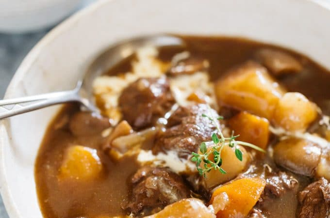 Instant pot beef stew served in a shallow bowl with a soup spoon and fresh cream drizzled over