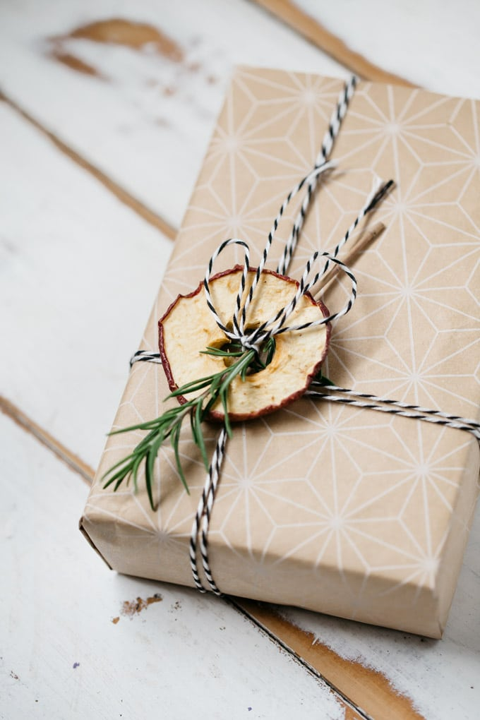 a box wrapped with natural coloured paper and tied with twine and dried apple and a rosemary twig