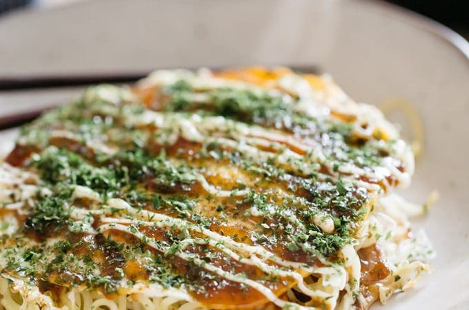 Hiroshima Okonomiyaki served on a round plate with a pair of chopstick