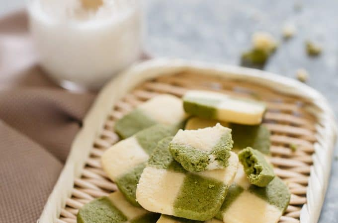 matcha cookies served on a bamboo tray with a glass of milk