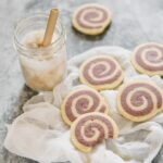 6 pinwheel cookies with purple sweet potato are scattered on with a glass of iced coffee