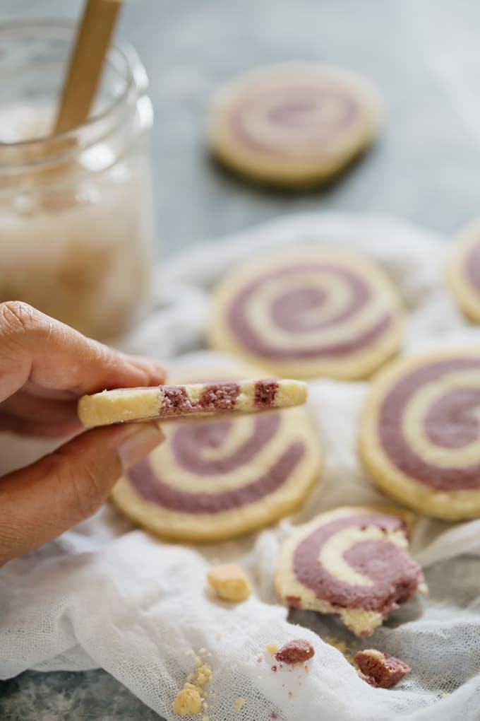 Pinwheel cookies scuttered on a table and one picked up by a hand
