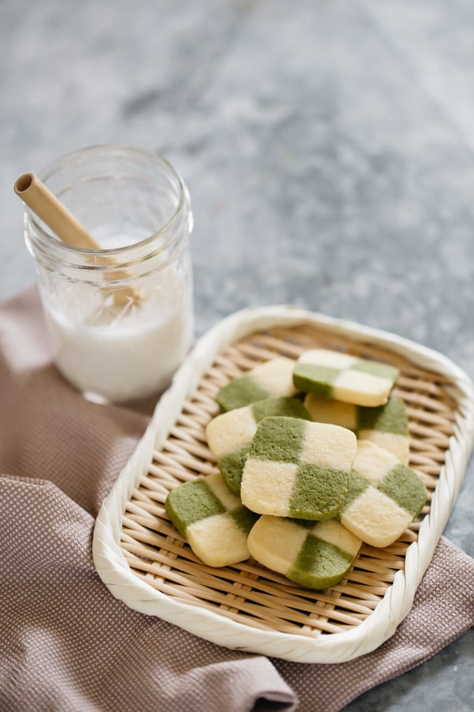Matcha cookies checkerboard pattern served on a bamboo tray with a glass of milk