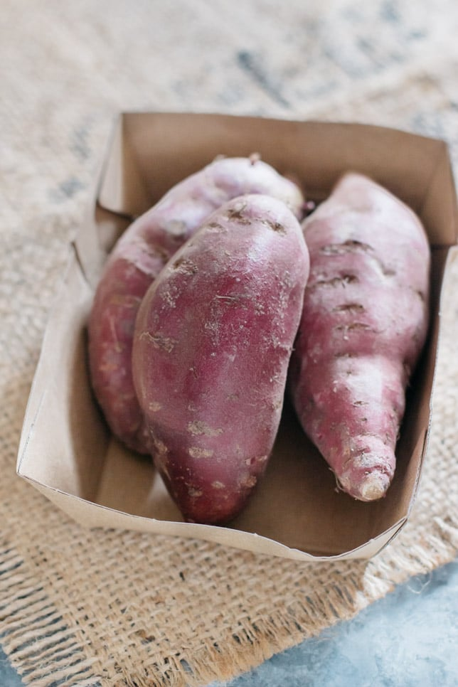 three purple sweet potatoes in a cardboard box
