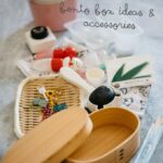 a wooden lunch box and bento box accessories in background