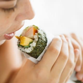 my son's girlfriend trying to eat whole sushi roll