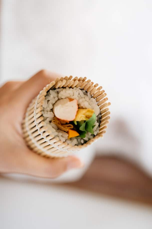 a hand holding a ehoumaki roll rolled in a bamboo sushi mat