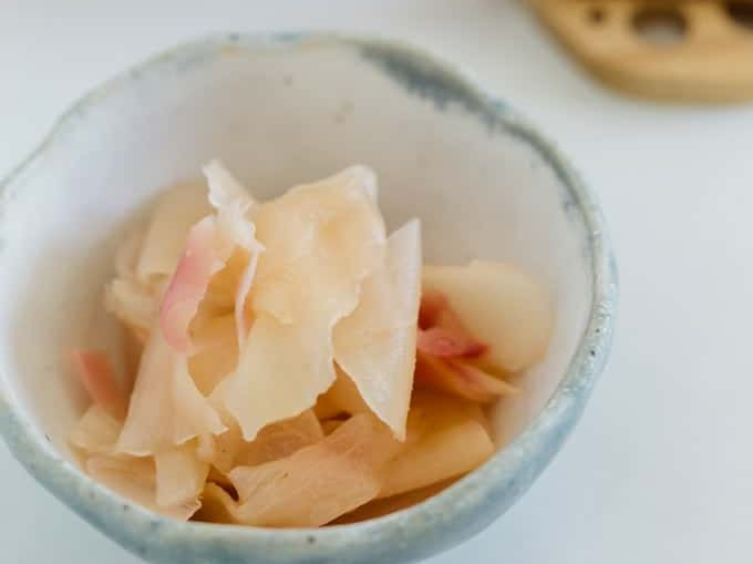 pickled ginger served in a small bowl and pickled ginger in a jar in background