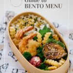 A complete bento in a wooden bento box with rice, deep fried prawns, nasu dengaku and potato chips