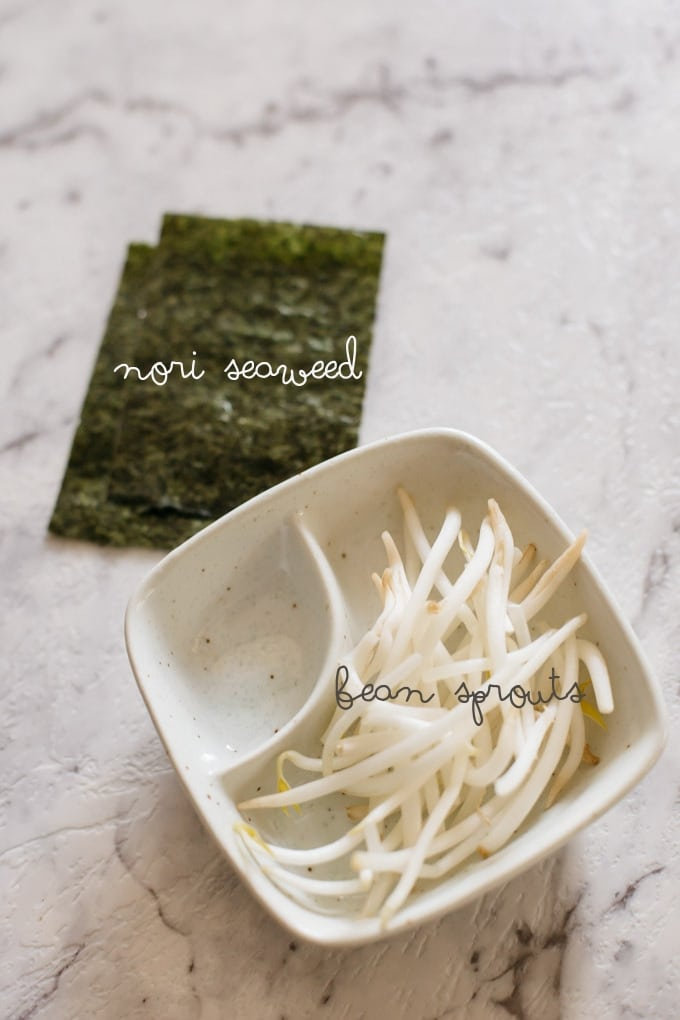 Shoyu ramen ingredients bean sprouts in a square bowl and two sheets of nori seaweed