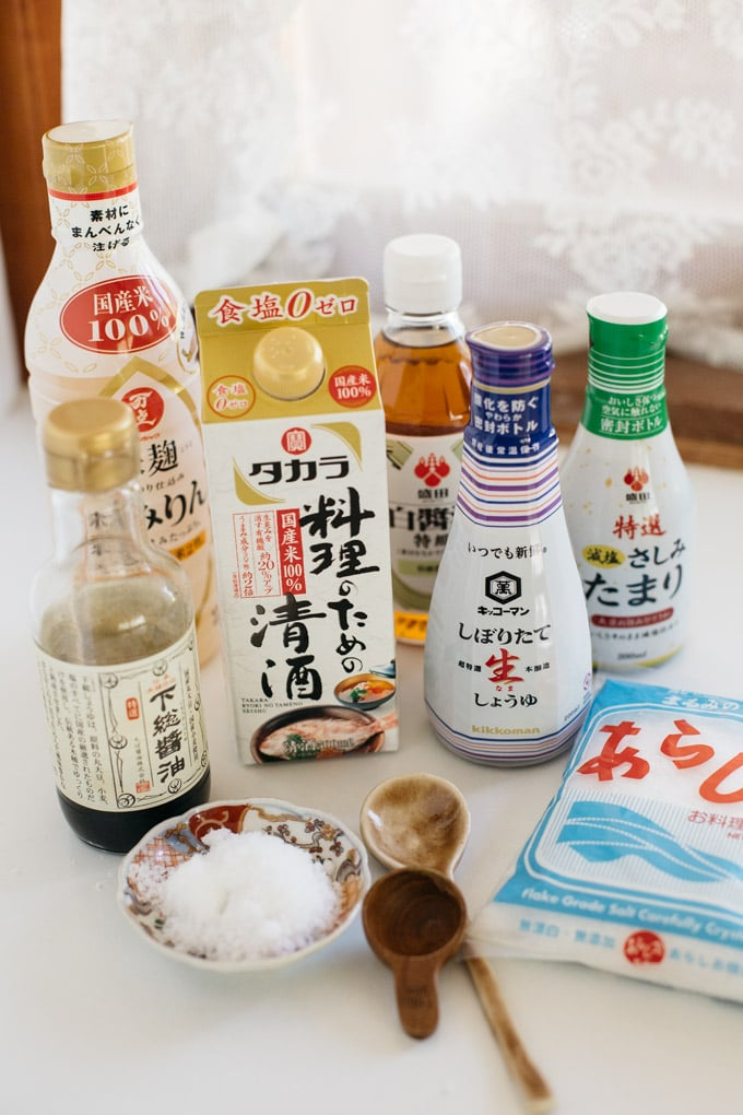 a bottle of mirin, 4 bottles of different types of soy sauce, a carton of sake, and a packet of salt