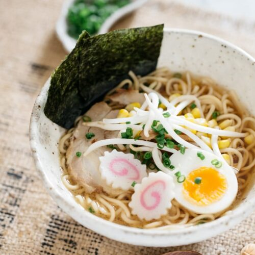 Shoyu Ramen served in a large white ramen noodle bowl with nori seaweed stick out