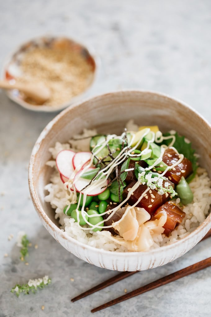 poke bowl dish is served in a Japanese pottery bowl with sesame seeds in a small bowl in background