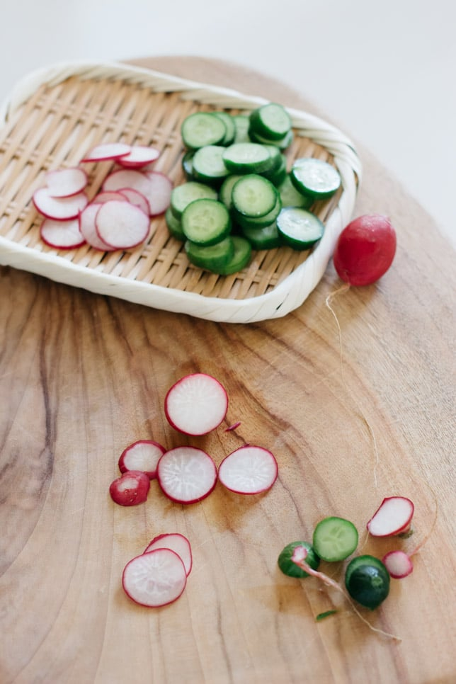 sliced cucumber and sliced raddish on a chopping board and a bamboo tray