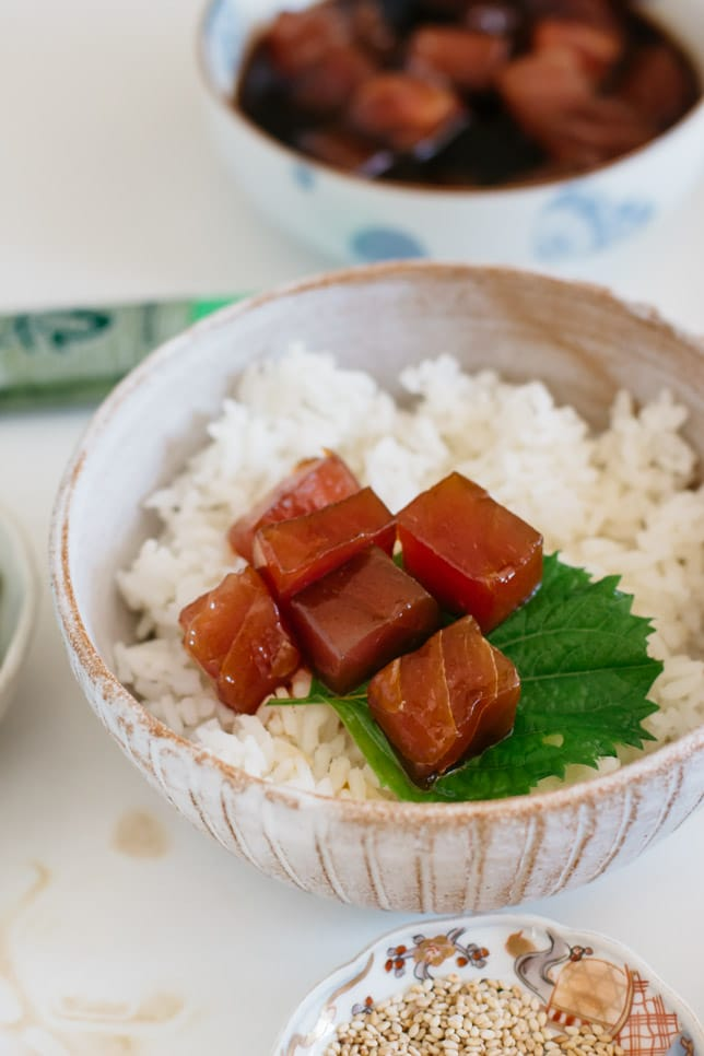 a bowl of rice and diced and marinated tuna on the rice with a shiso leaf