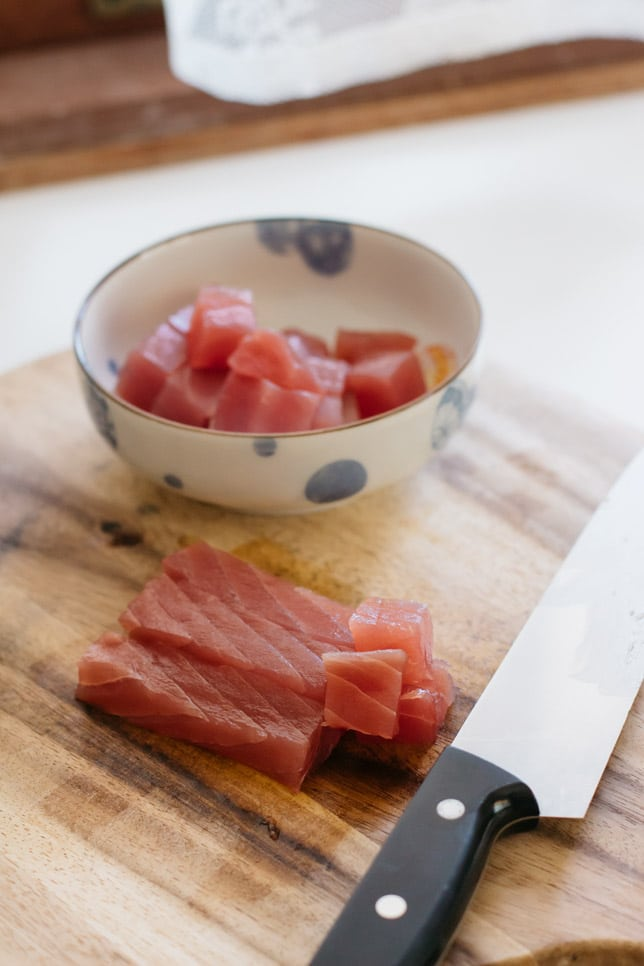 yellowfin tuna sliced and diced on a chopping board