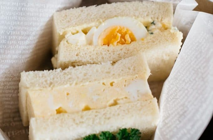 an egg omelette sandwich and an egg salad sandwich in a cardboard take away container