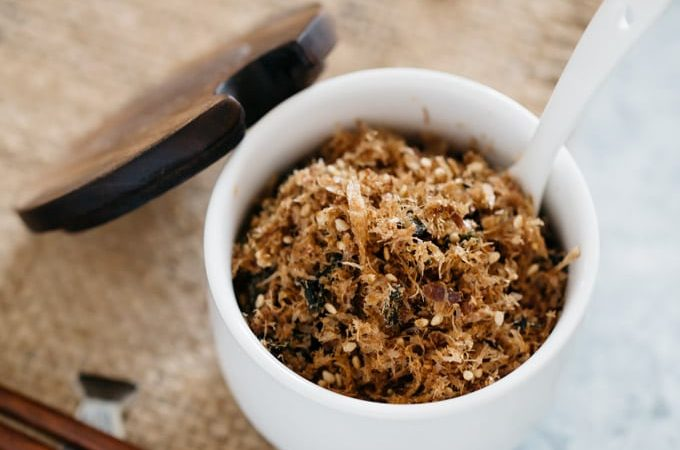 katsuo soft textured rice seasoning in a white container with a wooden lid and a pair of chopstick