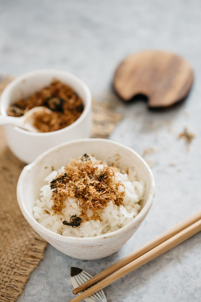 Furikake sprinkled over a bowl of rice with a pair of chopstick on the table and a container of furikake with a lid